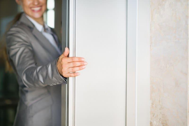 woman holding the elevator door open