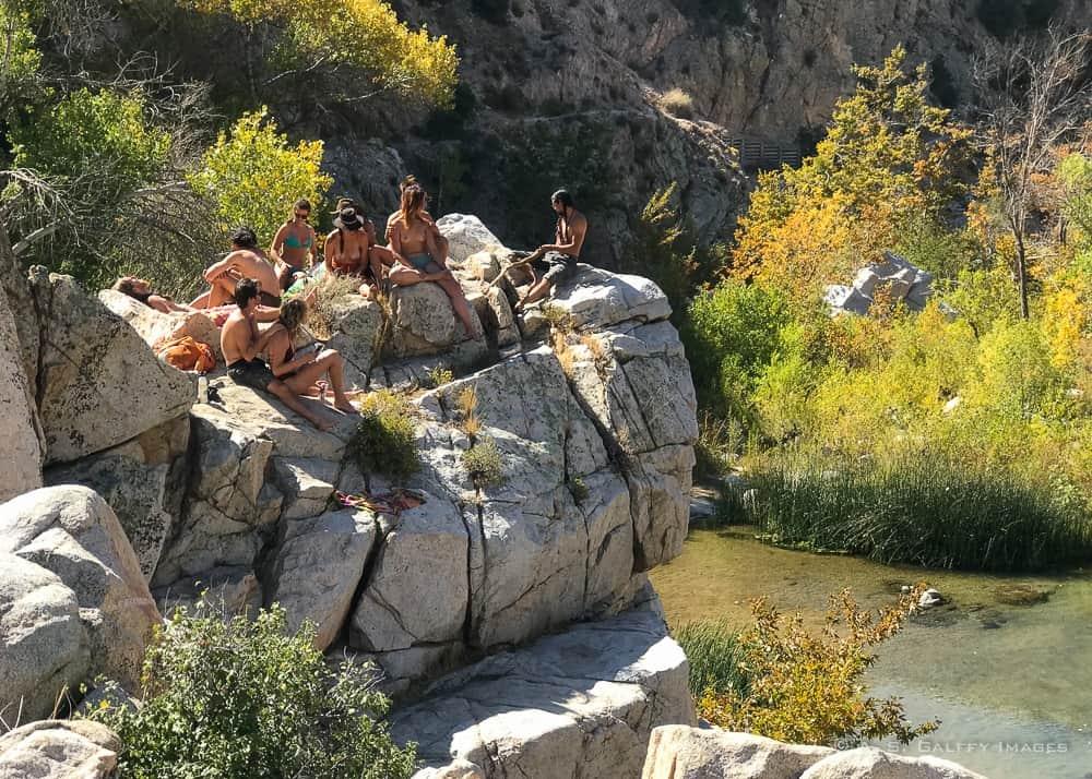 Nude people sunbathing on boulders