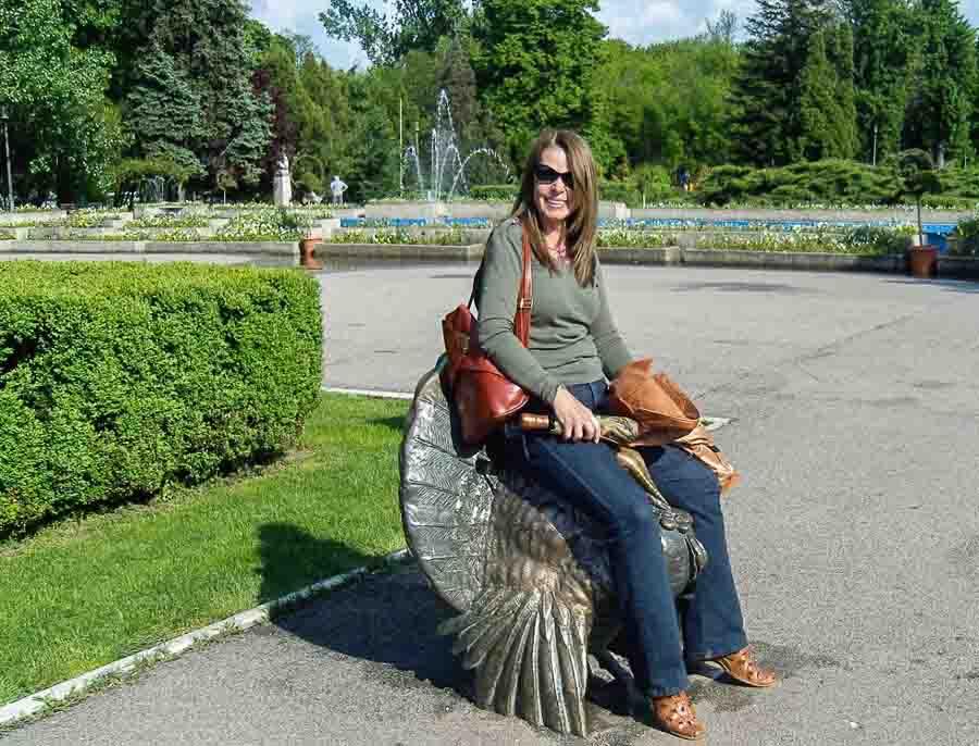 sitting on a bronze statue in Herastrau Park